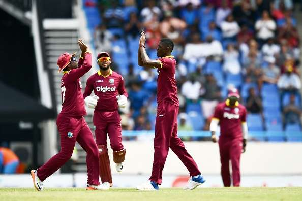Alzarri Joseph R celebrates with teammates after dismissing