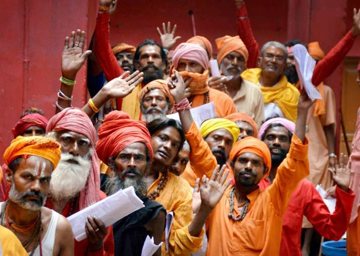 Jammu: Sadhus wait in a queue to register themselves for