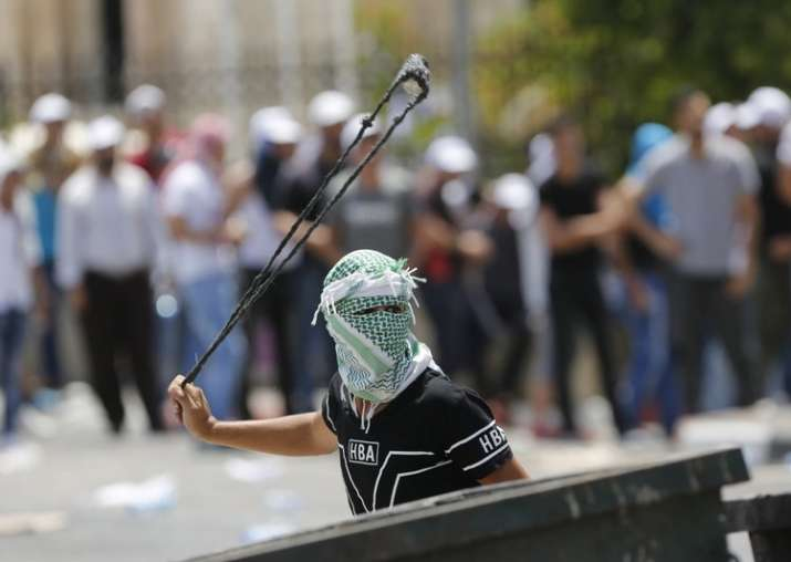 A Palestinian uses a slingshot against Israeli soldiers
