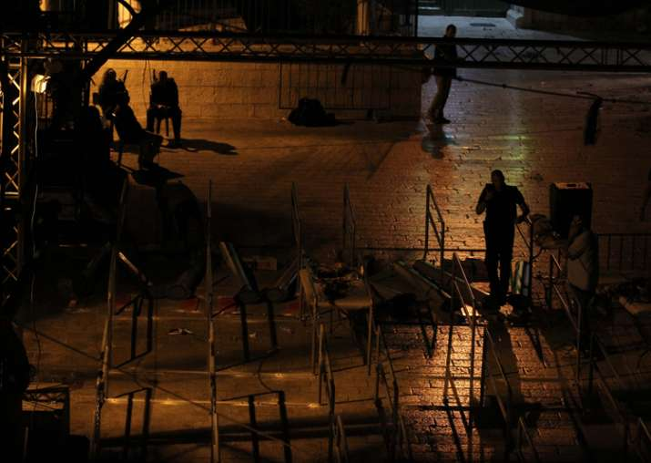 Workers dismantle metal detectors outside the al-Aqsa