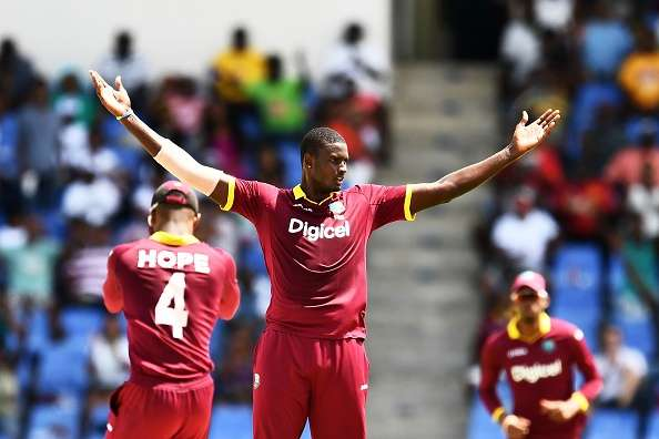 Jason Holder (C) celebrates after dismissing India's