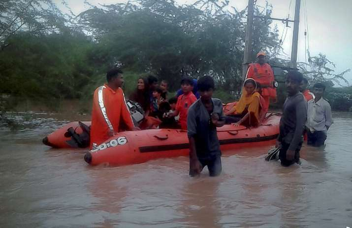 NDRF men rescuing people in a village in Gujarat's Morbi