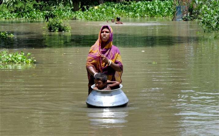 A woman with her child in flood affected Khanamukh village