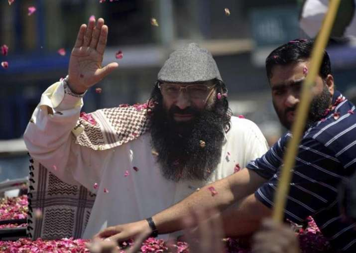 Syed Salahuddin waves to his supporters as he arrives in