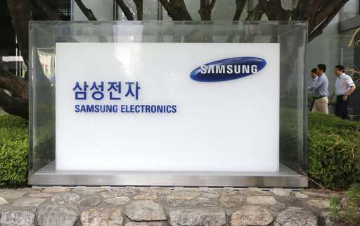 employees walk by the Seoul office of Samsung Electronics