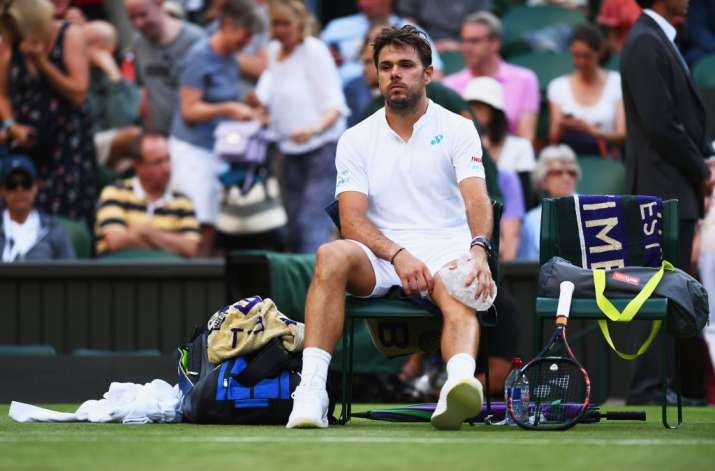 Stan Wawrinka of Switzerland puts ice on his knee during