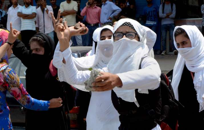 India Tv - Girl students throw stones at the security forces during a clash in Srinagar