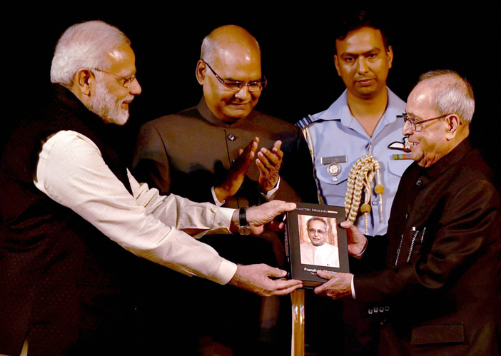 Modi handing a book to Mukherjee as Ram Nath Kovind looks