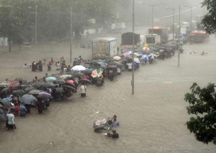 People walk along a flooded street during heavy rain