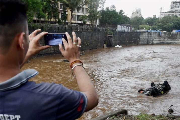 A man clicks picture of a car floating in a nullah in