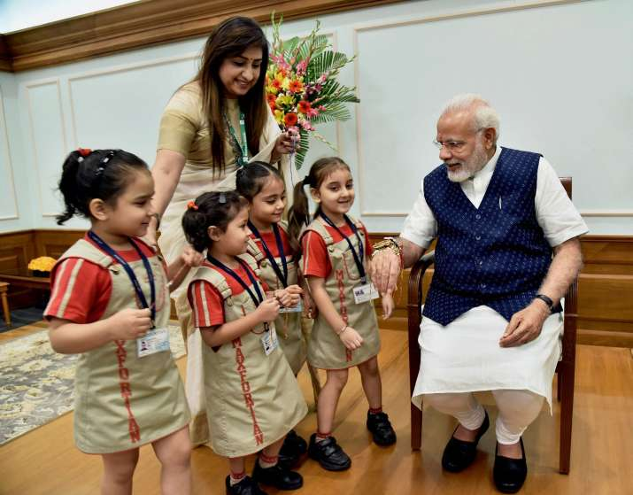 India Tv - School children tying rakhis on the wrist of Prime Minister Narendra Modi