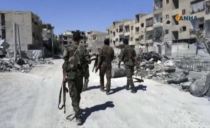 US-backed fighters patrol a street in Raqqa, Syria