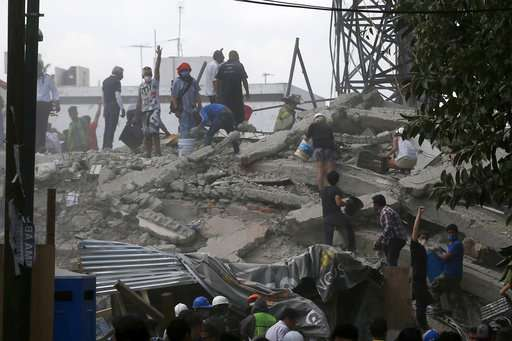 Volunteers search a building that collapsed after an