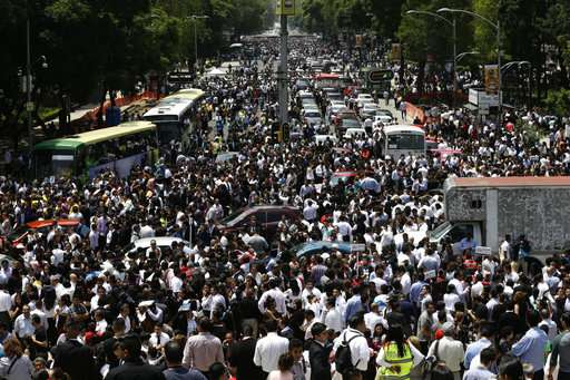India Tv - People evacuated from office buildings gather in Reforma Avenue after an quake.