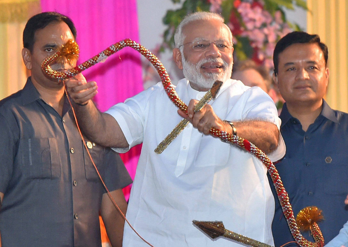PM Modi holds a bows and arrow during Dussehra celebrations
