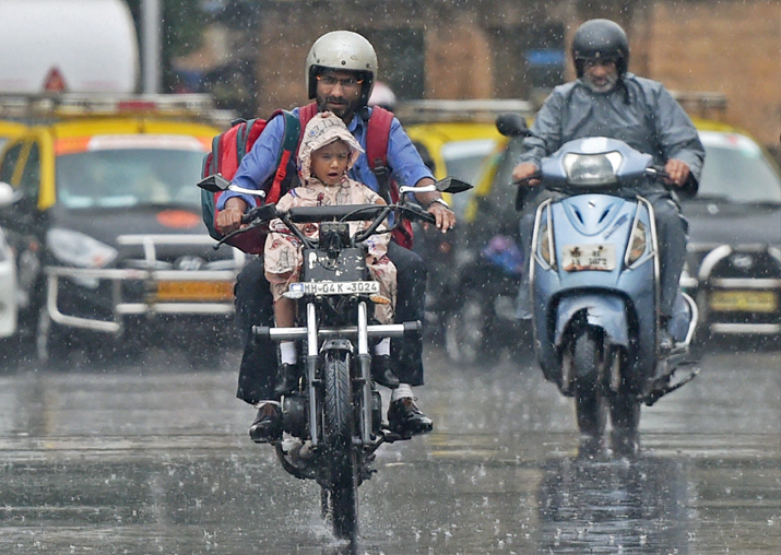 Mumbai: A man carries his child home from school on a
