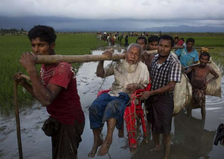 Ethnic Rohingya carry an elderly man and walk through