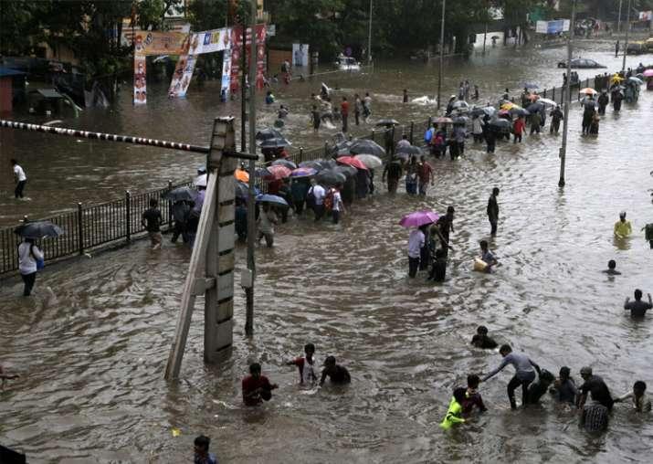 India Tv - People walk through a waterlogged street following heavy rains in Mumbai