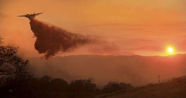 India Tv - A fire air taker makes a drop on a wildfire on the Hawkeye Ranch above Geyserville, California