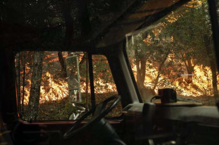 India Tv - Wildfire burning along the Highway 29 is seen through a fire truck Thursday