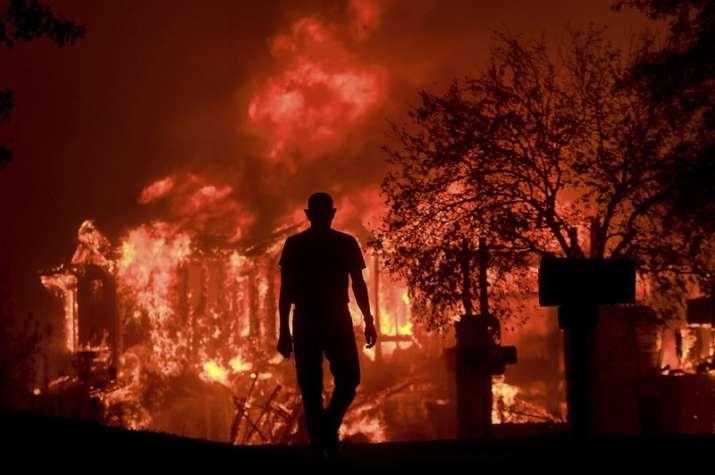 India Tv - A man watches part of his neighborhood burn in Fountaingrove, California