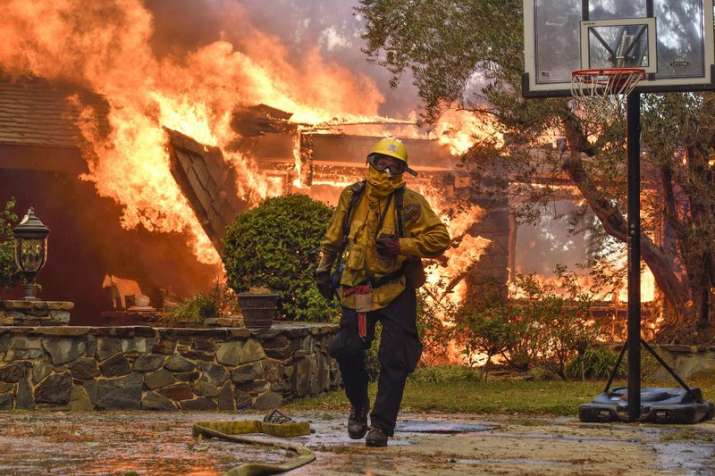 India Tv - Firefighters work to extinguish a fire at a home as they battle a wildfire in Anaheim Hills