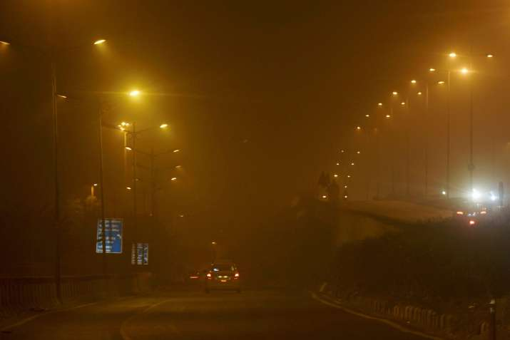 India Tv - Vehicles ply on smog covered street during Diwali night on Thursday.