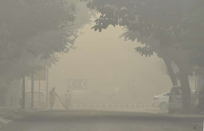 India Tv - A sweeper cleans a street as smog covers it in New Delhi on Friday morning, a day after Diwali.