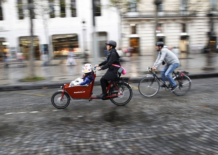 Pice - A woman and a man ride their bicycles on the Champs