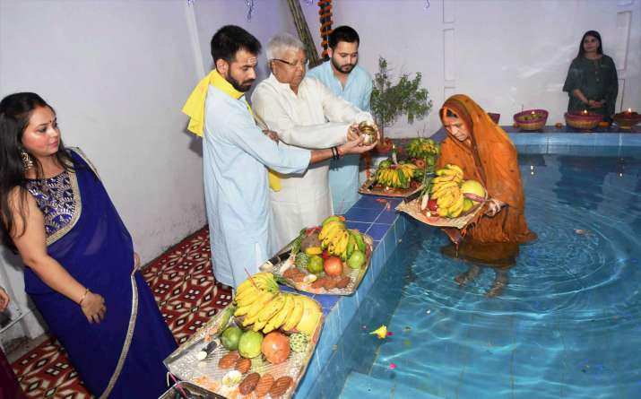 India Tv - Lalu Prasad with his sons Tej Partap Yadav, Tejaswi Yadav and wife Rabri Devi performing rituals during Chhath puja