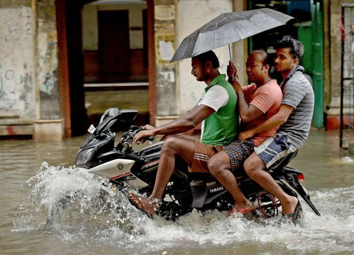 People on a motorcycle wade through a flooded street in