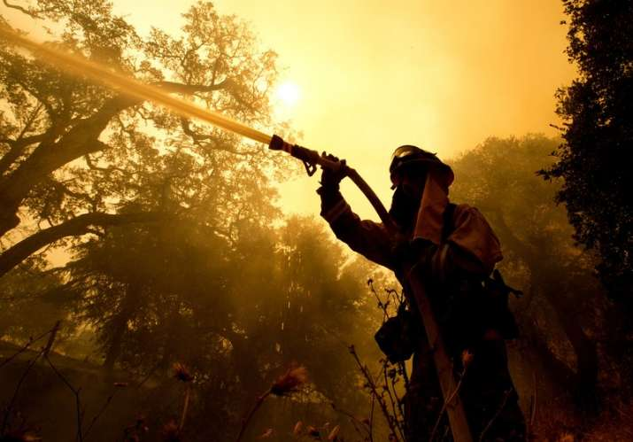 India Tv - Firefighter sprays water on a home as he battles flames from a wildfire Monday in Napa