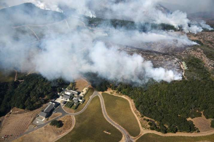 India Tv - Smoke rises as wildfire burns in the hills north east of Napa, California on Monday