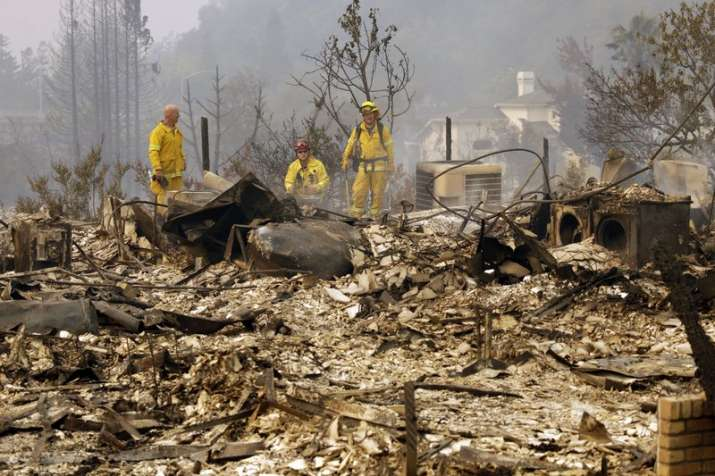 India Tv - Firemen look for hot spots in the Fountain grove area of Santa Rosa, California on Monday