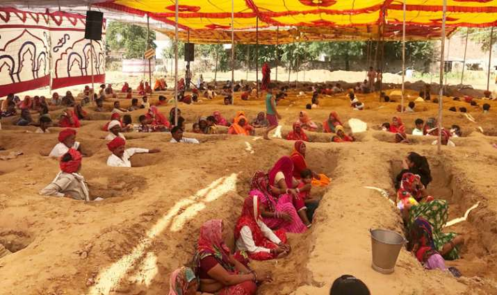 India Tv - Farmers, with bodies buried till neck in pits, protest against forced acquisition of their land at Nindar Village in Jaipur
