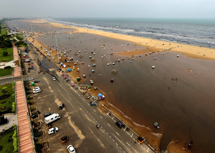 India Tv - People walk through a flooded area of Marina Beach on the Bay of Bengal coast after heavy rains in Chennai on Friday