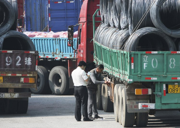 File - Chinese custom officials inspect trucks loaded with
