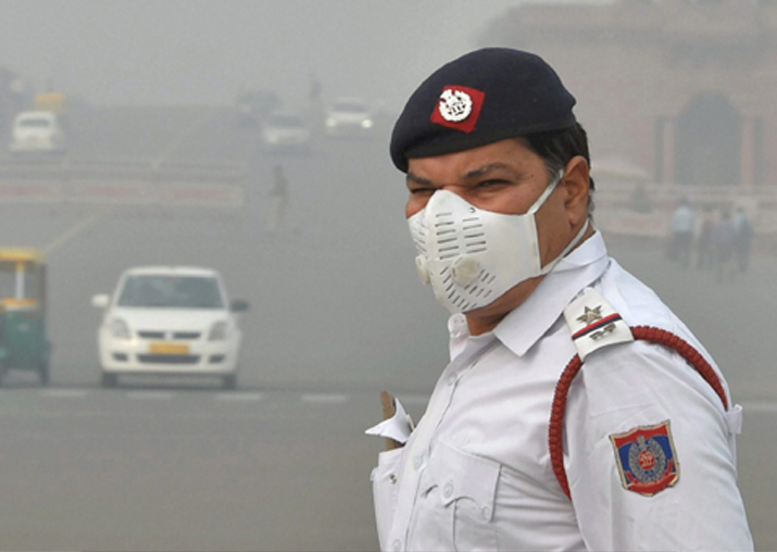 A traffic policeman, wearing an anti-pollution mask, mans