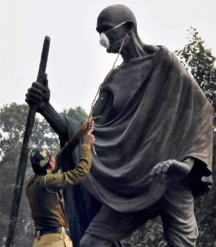 India Tv - A policeman removes the anti-pollution mask from the Gandhi Statue at Gyarah Murti which was put by Kapil Misra