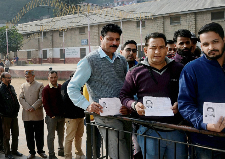 Voters in a queue show their voter identity card at a