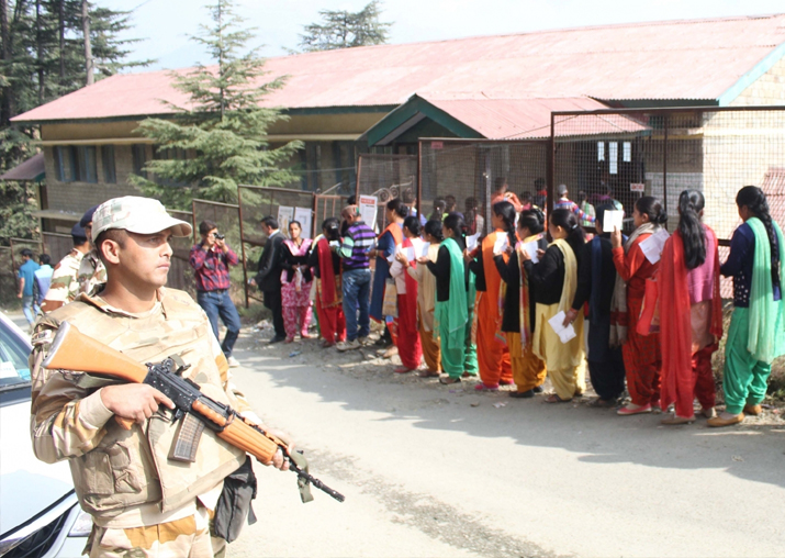 Voters wait in a queue to cast their votes during Himachal