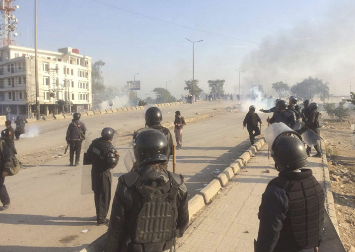 India Tv - Smoke rises as Pakistani police officers fire tear gas shell to disperse protesters during a clash in Islamabad