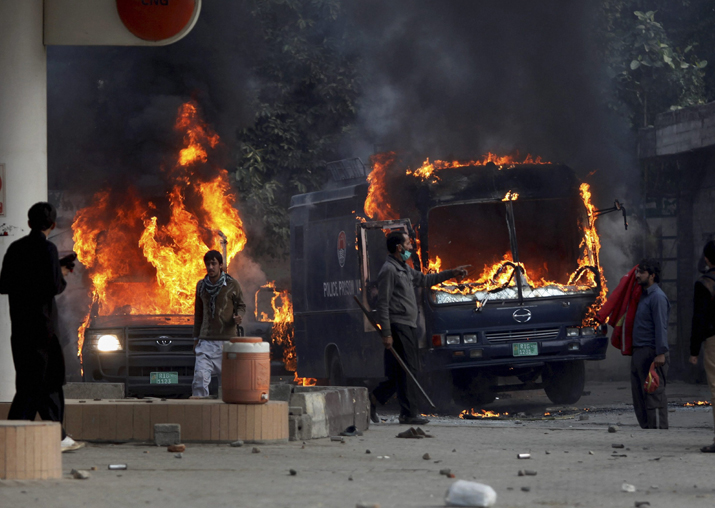 India Tv - Pakistani protesters gather next to burning police vehicles after setting on fire them during a clash in Islamabad
