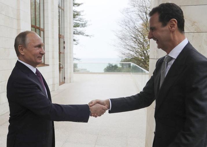 Vladimir Putin shakes hand with Bashar Assad in the