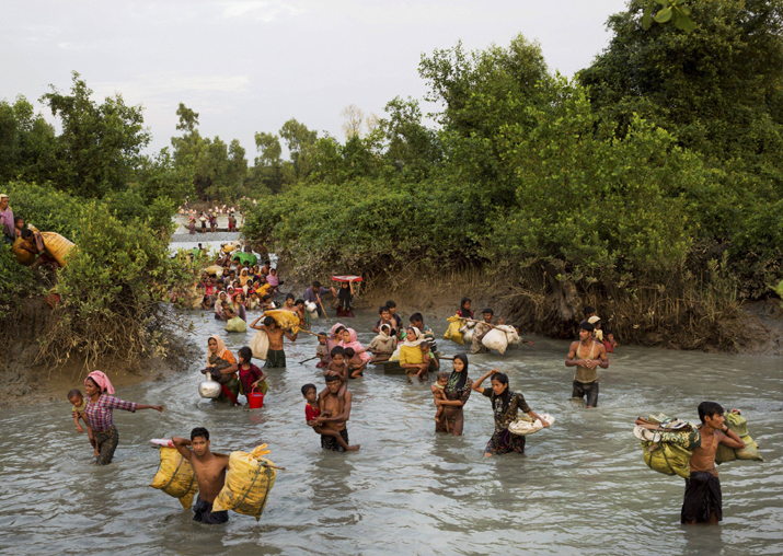 Rohingya wade through the Naf river after having just