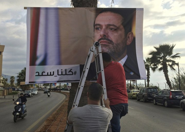 Workers hang a poster of outgoing PM Saad Hariri with