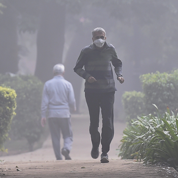 India Tv - A man, wearing an anti-pollution mask, jogs through smog at Sanjay Park in New Delhi