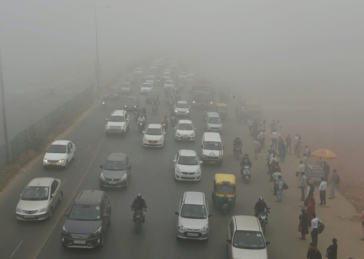 Vehicles plying at a road in smog, in New Delhi