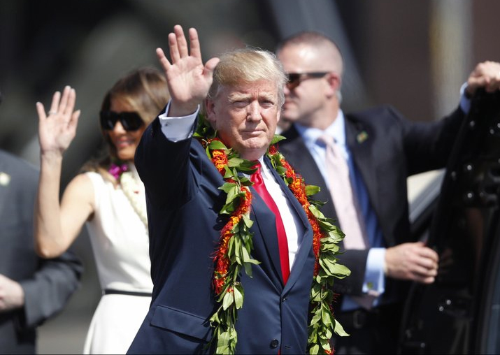 India Tv - Adorned with lei, Donald Trump walks towards the motorcade with first lady Melania Trump to meet servicemen