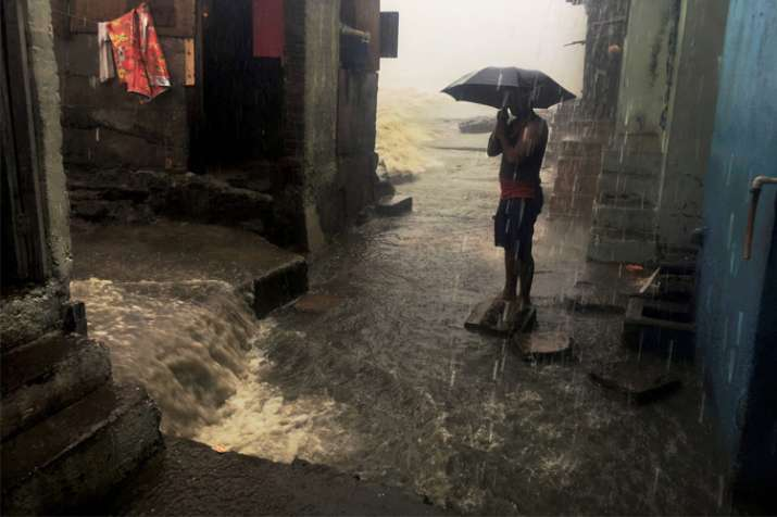 India Tv - A man stand with an umbrella in a street amid heavy showers triggered by cyclone Ockhi in Mumbai.